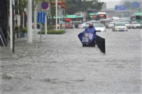 pict-20日、大雨に襲われた中国の河南省鄭州市で、冠水した道路に立ち尽くす住民.jpg