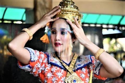 pict-dancer at the Erawan Shrine puts on a face shield.jpg